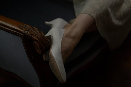 Close Up Photo of Person Wearing White Leather Heels