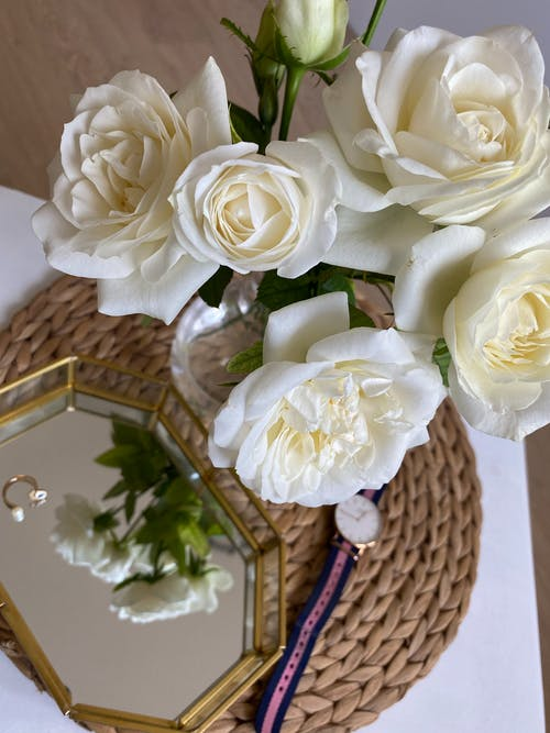 Blooming rose bouquet reflecting in mirror on table