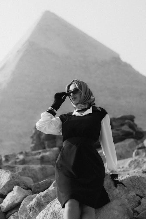 Woman in Black Dress Standing on Rock