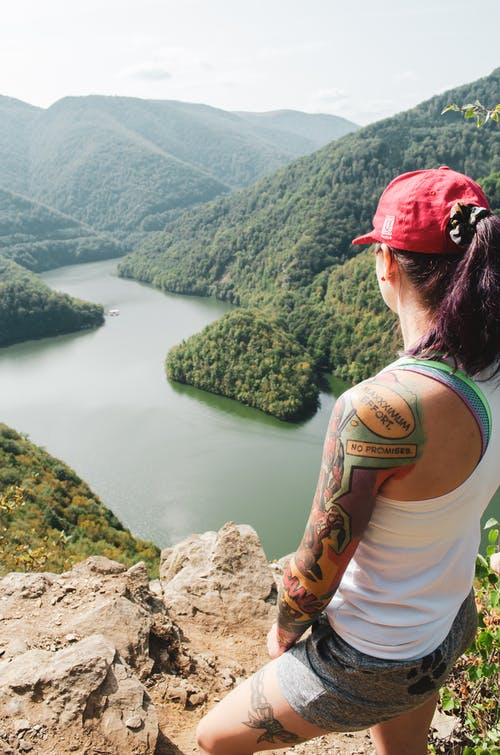 Woman in White Tank Top and Red Cap Sitting on Rock Looking at River