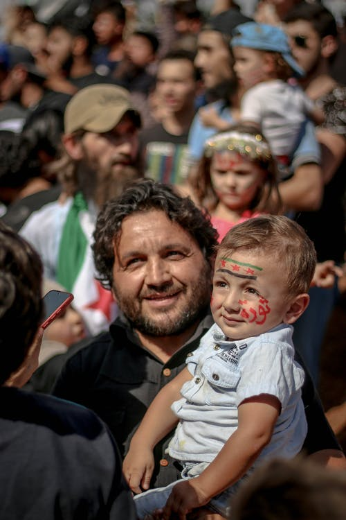 Positive ethnic man carrying son with painted Syrian flag and Arabic lettering on face at opposition rally