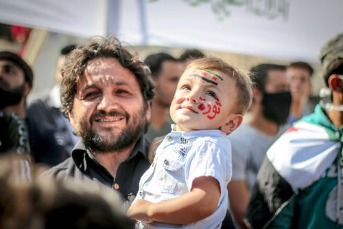 Ethnic bearded man carrying small kid with painted face in crowd of protesting against policy