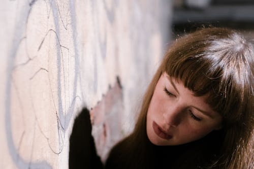 Crop dreamy adolescent near graffiti wall in city