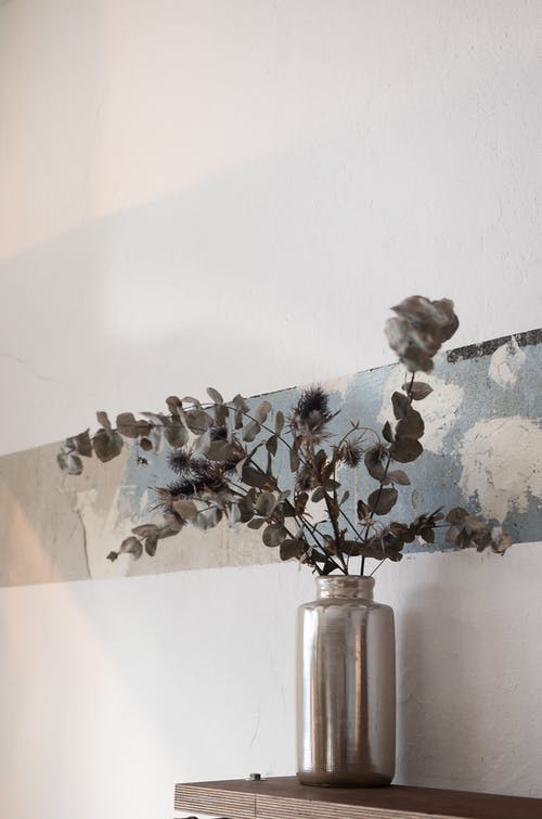 Shiny vase with dried plant sprigs with small leaves on wooden shelf near wall at home