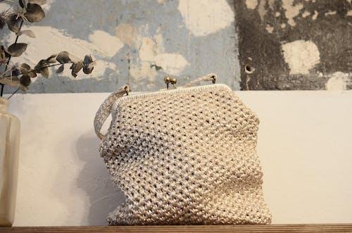 Woolen handbag on table near wall at home