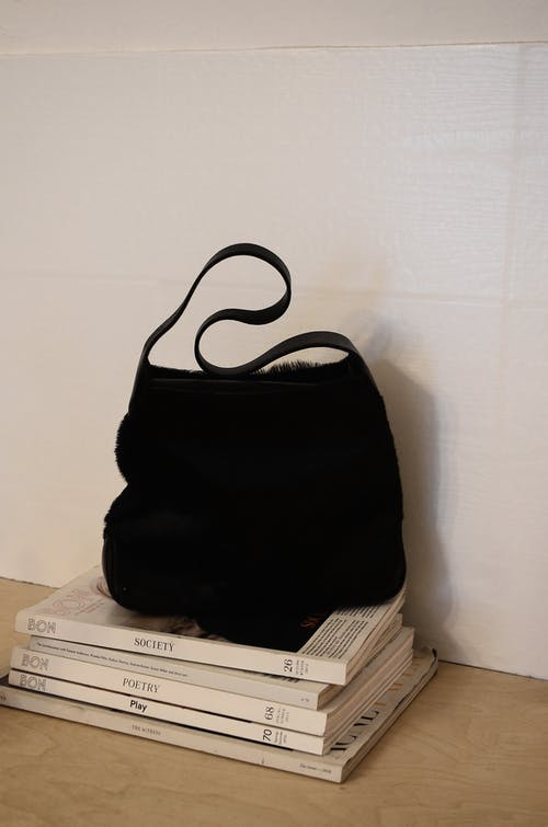 Black loose handbag placed on stacked books and journals on table against white wall