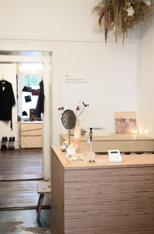 Stylish interior design of modern light clothes store or atelier studio with wooden counter and changing room