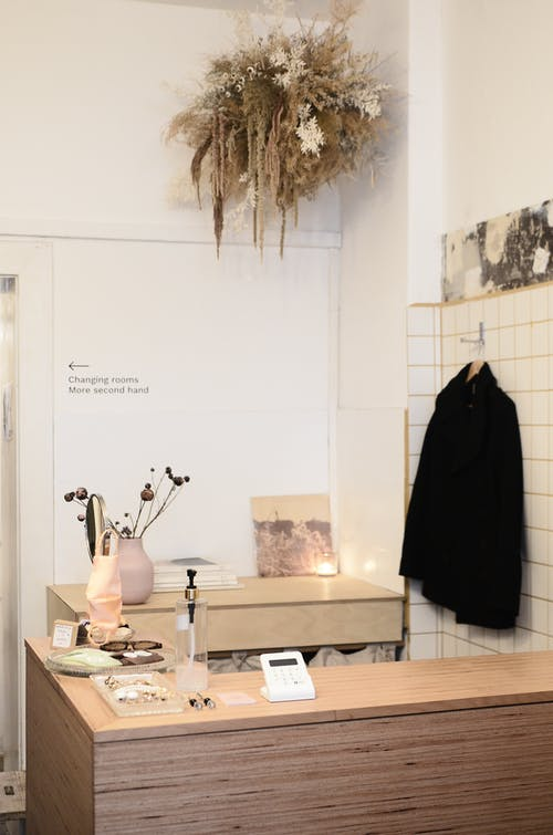 Interior of contemporary light clothes store or atelier studio with dry decorative plants on wooden counters