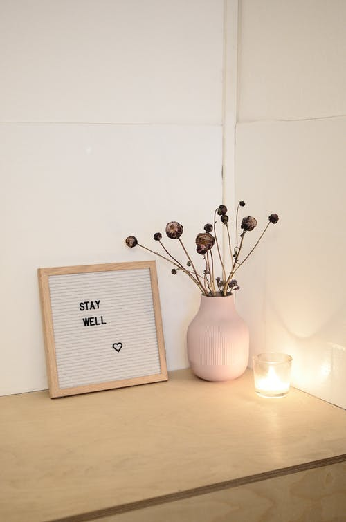 Wooden cabinet top with framed image with inscription Stay Well and dry plants in white vase near burning candle