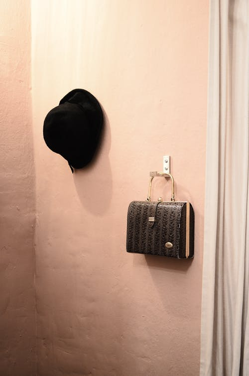 Black hat and bag hanging on hooks in wardrobe