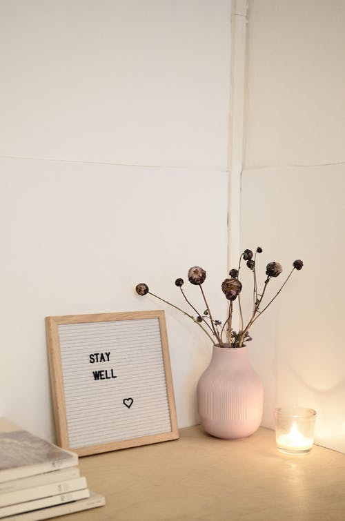 Corner of cozy room decorated with dry flowers in vase near frame with words stay well and stack of magazines