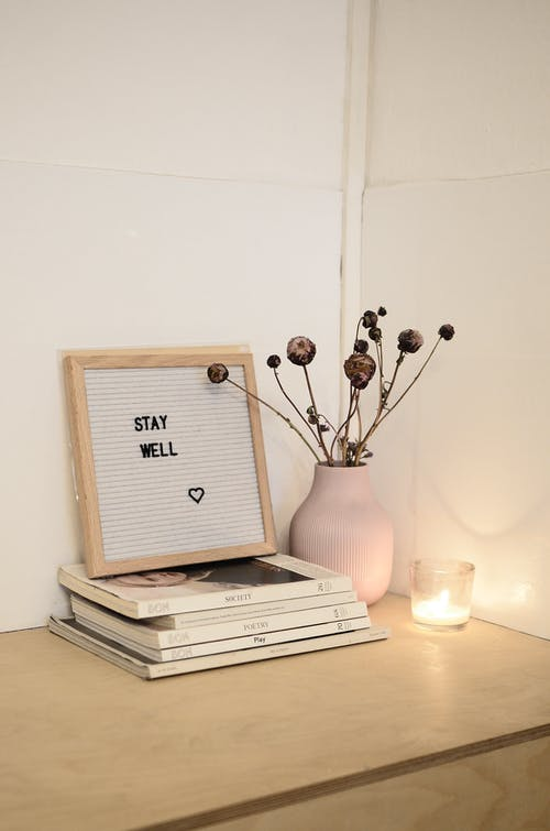 Frame with words on stack of magazines near vase