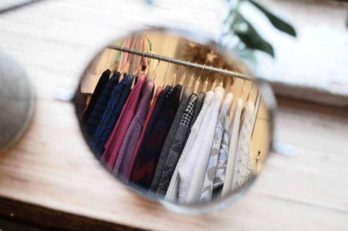 Clothes hanging on rack in reflection of mirror