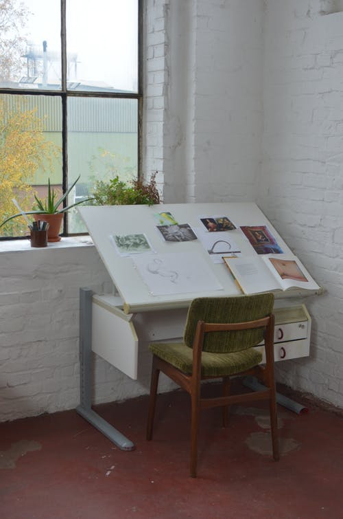 Chair placed near window and table with drawings