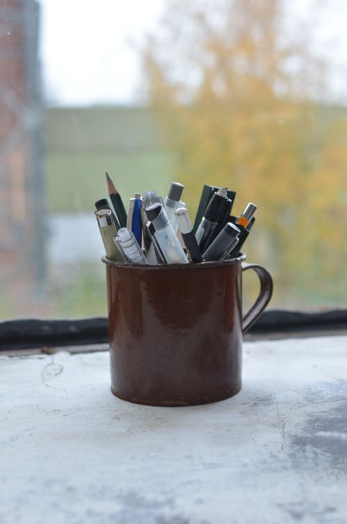 Cup with various stationery consisting of pencils and pens placed on windowsill near window in art workshop