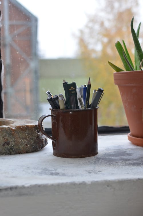 Cup with pencils on windowsill near potted plant