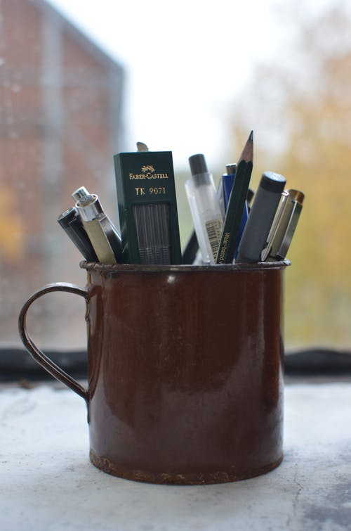 Cup with supply for writing and creating artworks placed on windowsill in workshop
