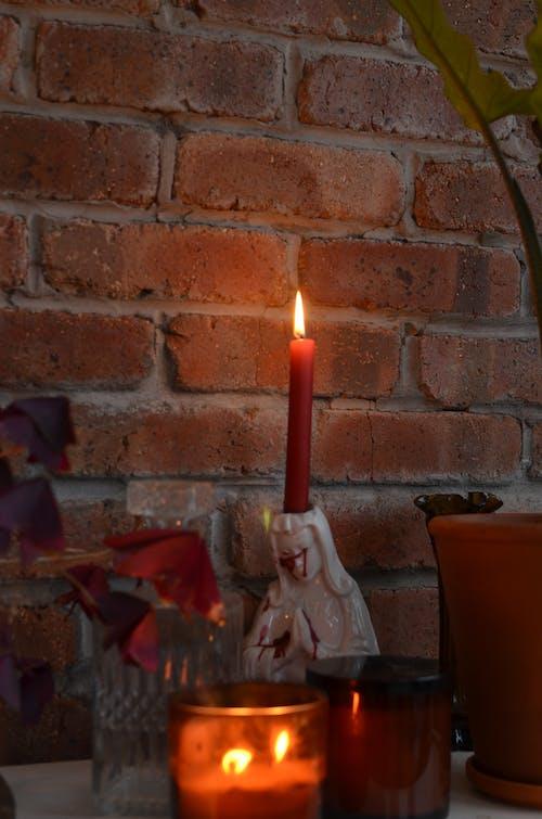 Burning candles at brick wall