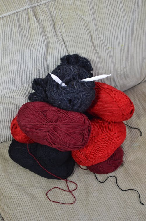 Knitting supplies placed on sofa at home
