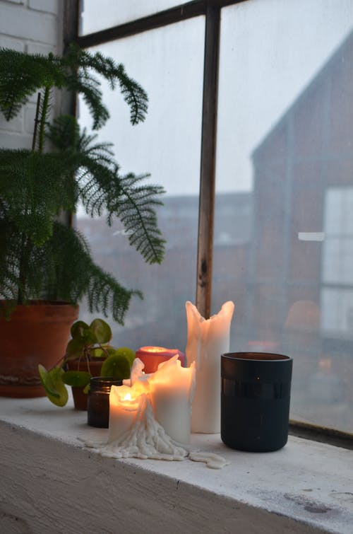 Burning candles with plants on windowsill in house room