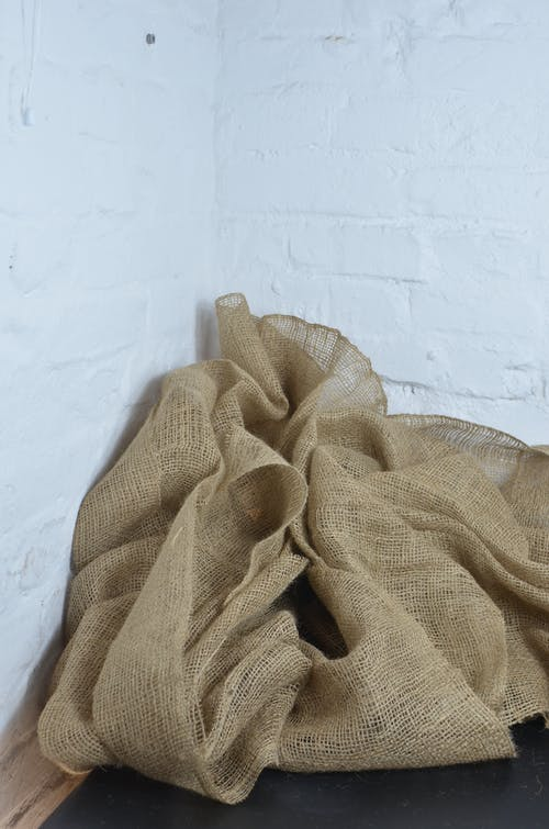 Creased organic burlap near white walls at home