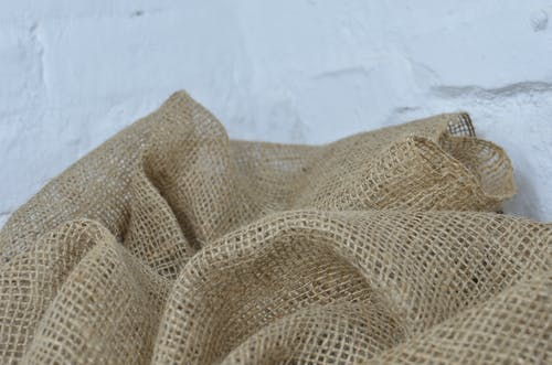 Crumpled sackcloth with thin fibers on white background
