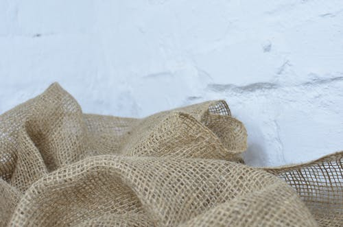 Crumpled sackcloth with ornament on white background