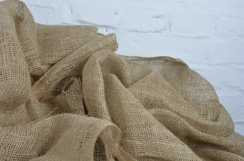 Crumpled organic sackcloth on rough white background