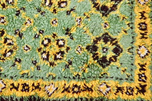 Top view of abstract backdrop representing colorful soft rug with geometric decor in daylight