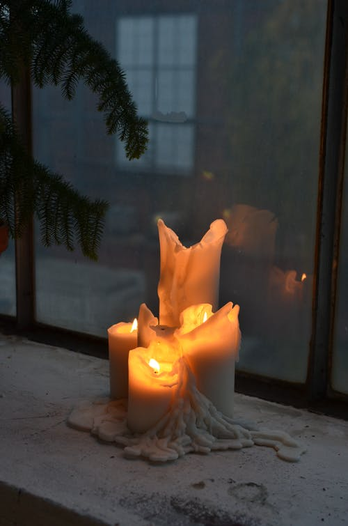 Burning candles on windowsill at home in evening