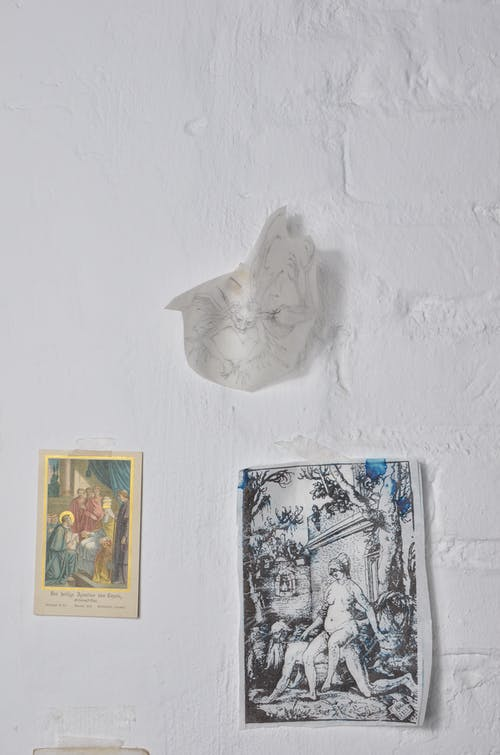 Postcard and paper with pictures on whitewashed wall