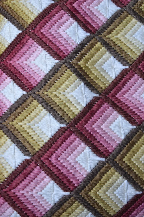 Top view of textured backdrop representing colorful soft textile with geometric ornament in daylight