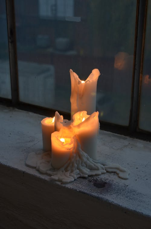 Burning candles on windowsill at home in twilight