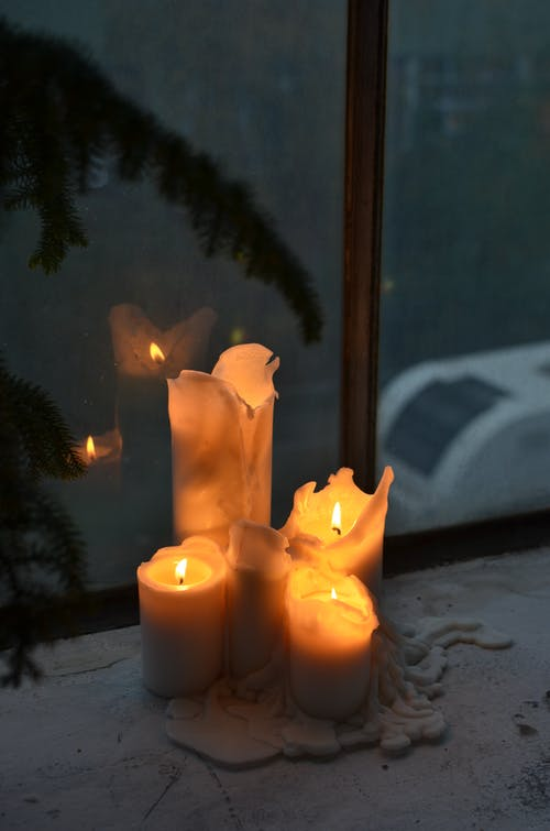 Burning candles with melted wax near plant leaf silhouette on windowsill at home in darkness
