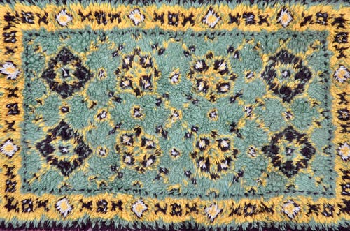 Textured soft warm oriental styled carpet with symmetric geometric ornament as abstract background
