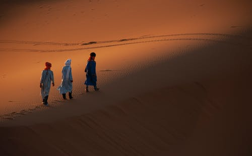 Group of People Walking on a Desert