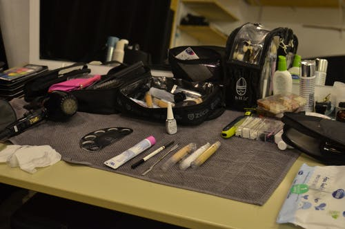 From above of hair dryer and cosmetic bags with various makeup supplies and products placed on table in dressing room