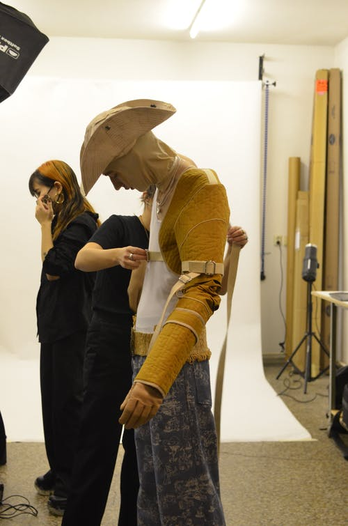 Stylist tying belts of modern stylish outfit on model while preparing for photo shoot in studio