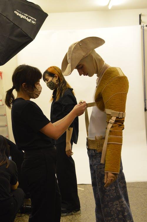 Stylist preparing model for photo shoot in studio