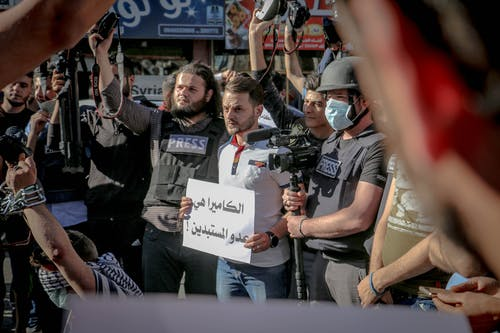 Group of ethnic journalists with placard with Arabic inscription and cameras at demonstration against policy