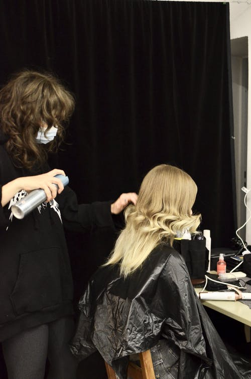 Side view of stylist in mask creating stylish hairdo with spray for model in dressing room