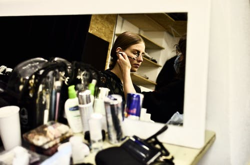 Reflection of female visagiste with brush applying makeup on face of model in dressing room