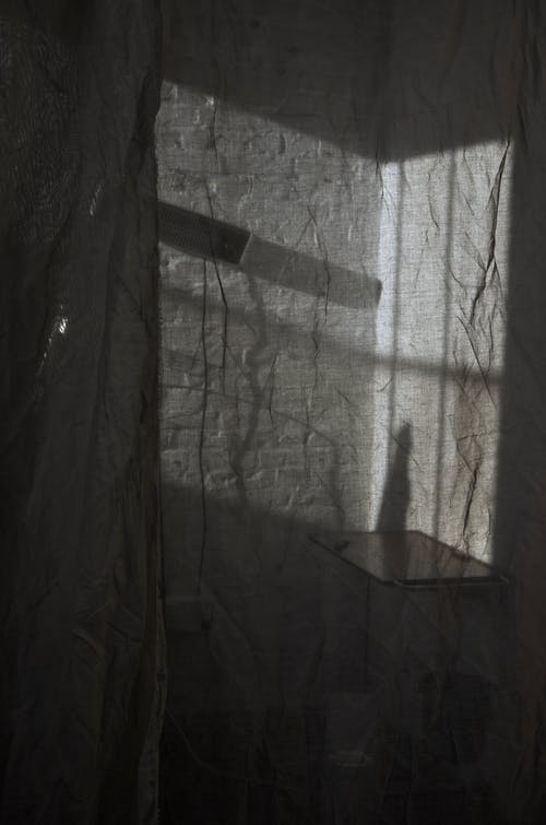 View through transparent crumpled curtain with table and lamp hanging on white brick wall