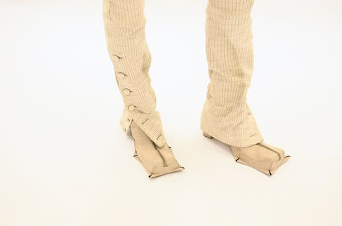 Crop model in stylish boots and ornamental trousers