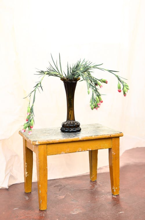 Blossoming flowers in decorative vase on table at home