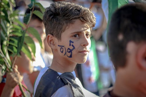 Side view of ethnic teenage boy with Arabic inscription on face standing on crowded street at protest movement against state policy