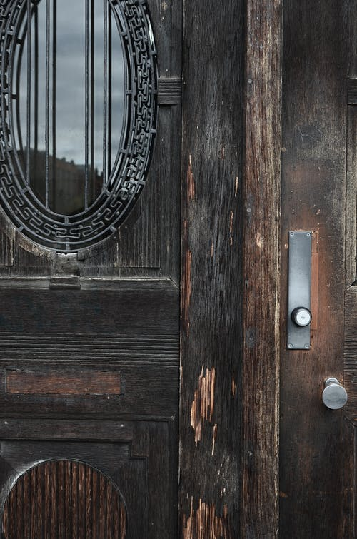 Shabby aged wooden doors with scratches at entrance of damaged worn out house