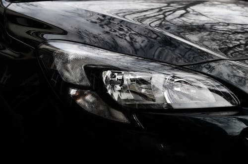 Polished reflecting surface of black modern car hood with glossy headlight on street