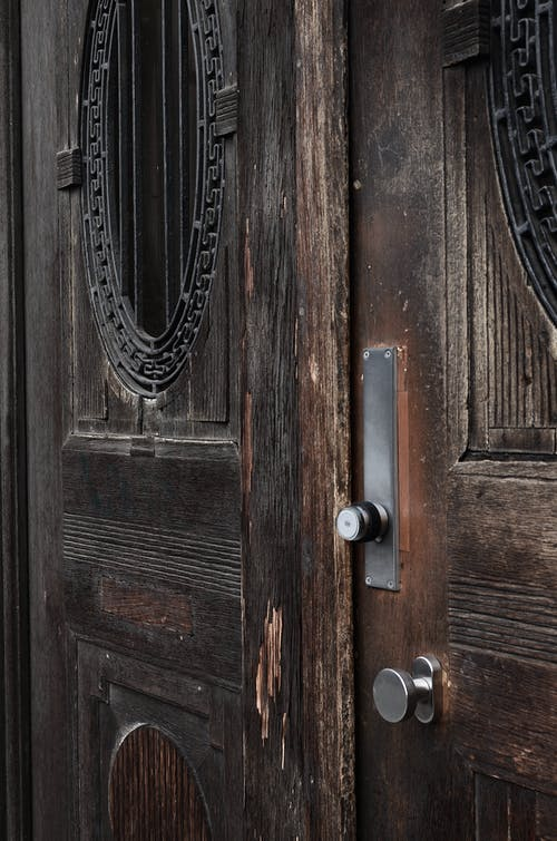 Closed old fashioned doors made of brown wood with damaged surface and metal handles