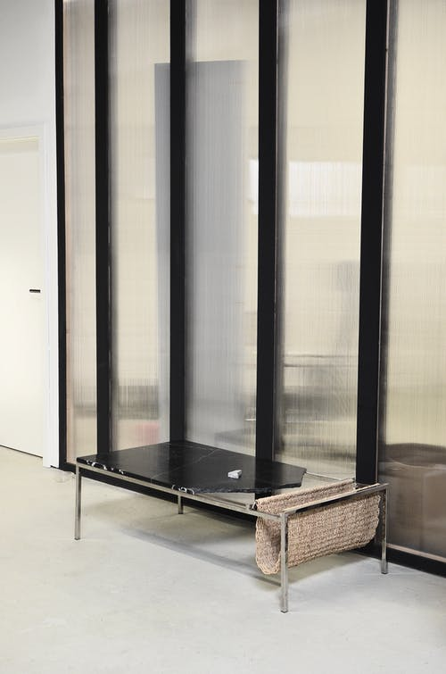 Interior of hallway with seat placed against glass wall in modern office building